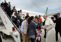 epa05262088 Pope Francis (R) welcomes a group of Syrian refugees that flew with him after landing at Ciampino airport in Rome, Italy, 16 April 2016. Pope Francis is taking twelve Syrian migrants with him to the Vativan after a visit to the Greek island of Lesbos on 16 April, in a trip aimed at supporting refugees and drawing attention to the frontline of Europe's migration crisis.  EPA/FILIPPO MONTEFORTE