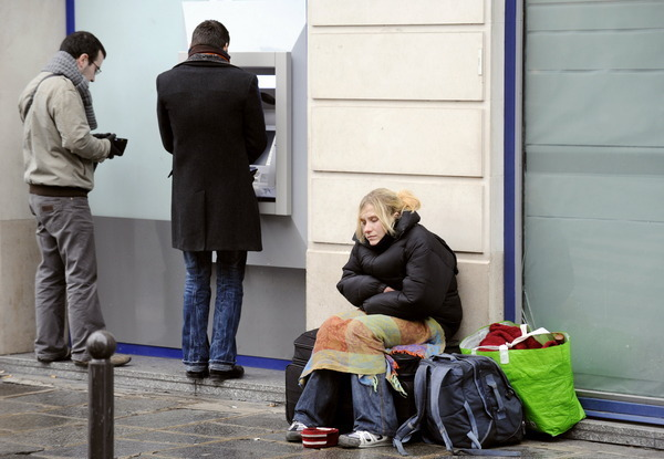 People take out money near a beggar in a Paris street on December 30, 2008. While many people go about shopping for new year's eve, others are focused on finding a warm and safe place to sleep as temperatures in this time of the year fall under the zero causing the death of homeless people who don't find appropriate shelter. AFP PHOTO BERTRAND GUAY